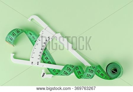 Green Measuring Tape And White Caliper. Top View, Copy Space.