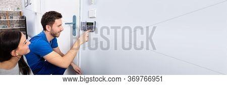 Alarm System Security Installation At Home. Technician Installing Near Door