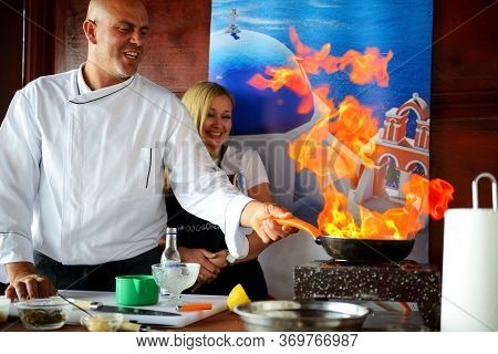 Santorini, Greece - May 18: The Cooking Of Traditional Greek Dishes By Chef With Help Of Tourist Is