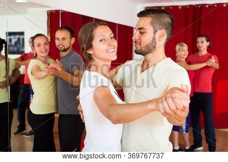 Handsome Man Dancing A Slow Dance With A Sexual Smiling Woman In A Dancing School. Two Couples Danci