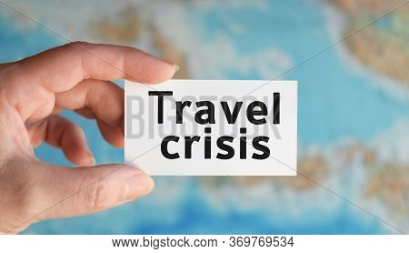 Travel Crisis - Text On A White Sheet In Hand Against The Background Of The Atlas Map