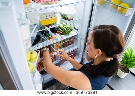 Women Looking For Food Inside Fridge In Kitchen
