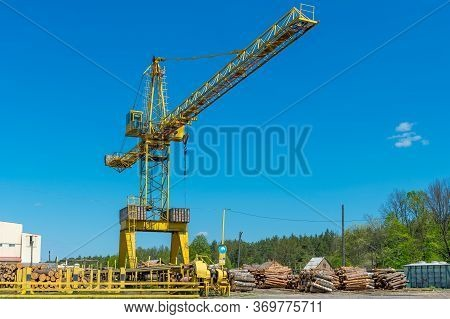 Large Industrial Crane Over Piles Of Freshly Cut Logs At The Sawmill Factory