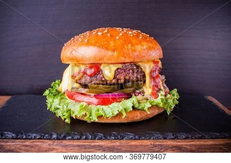 Craft Beef Burger With Beef, Jalapenos, Sauce Salsa, Cheese, Fresh Vegetables On A Board With A Ston