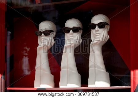 Fashionable Mannequins On A Red Background. Mannequins With Sunglasses On
