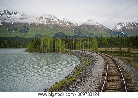 Railroad Tracks Landscape With Alaska Mountain Ranges And Lakes