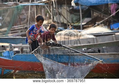 Siem Reap, Cambodia - 17 01 2019 - Children Pull Fishing Net Out Of Tonle Sap Lake, The Floating Vil