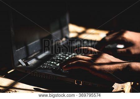 The Hacker Using His Laptop Computer To Open Dark Web Sites At Indoor Dark Room..