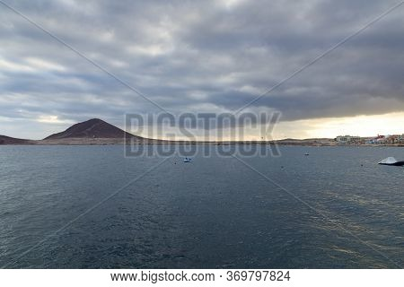 Bay Of El Medano Panorama With Kitesurfers, Atlantic Ocean And Dark Clouds On Canary Island Tenerife