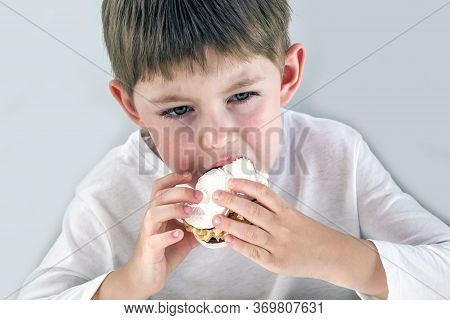 Blond Little Boy With An Appetite Eats A Delicious Sweet Cake. Junk And Unhealthy Food. Blurry, Sele