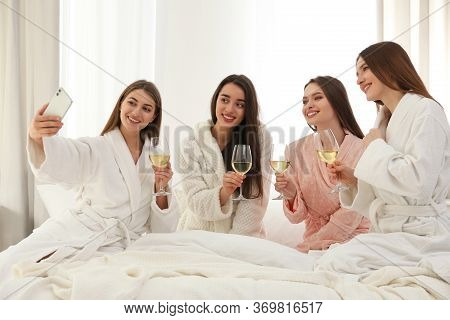 Beautiful Young Ladies With Glasses Of Wine Taking Selfie On Bed At Pamper Party. Woman's Day