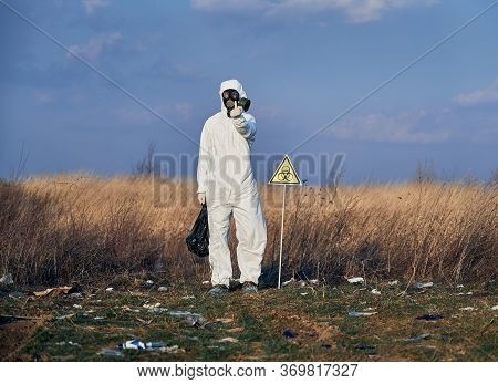Full Length Of Angry Environmentalist In Protective Suit Standing In Field With Garbage And Biohazar