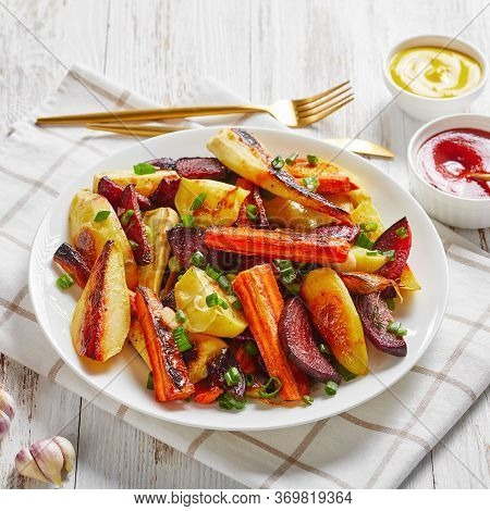 Close-up Of Grilled Sliced Beetroot, Potato Wedges, Parsnips, Carrots Sprinkled With Chopped Green O