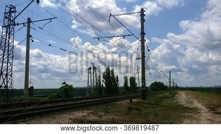 Railway Track With High Voltage Wires In The City Of Zaporozhye. Against The Background Of Clouds. S