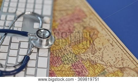 Keyboard, Medical Stethoscope And A Protective Mask On A Geographical Map. Concept Stay Home And Rem
