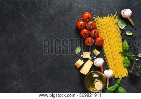 Ingredients For Making Pasta. Raw Spaghetti With Tomato And Basil On A Black Background. View From A