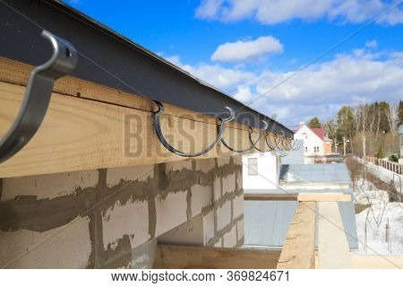Close Up View Of House Under Construction With Holders For Gutters Water Drainage System