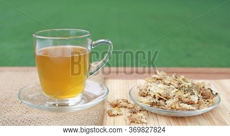 Chrysanthemum Juice In Glass Cup And Dried Chrysanthemum Flower On Wood Background Against Green Gra