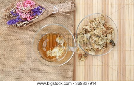 Top View Image Of Chrysanthemum Juice With Dried Chrysanthemum Flower On Sack And Wood Mat.