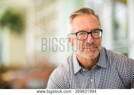 Mature Handome Fit Man Sitting Outside Stock Photo