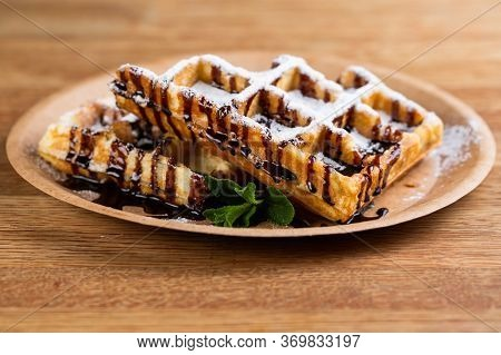 Viennese Waffles On A Disposable Plate With Peanut Butter, Icing Sugar And Mint.