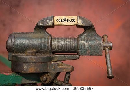 Concept Of Dealing With Problem. Vice Grip Tool Squeezing A Plank With The Word Obedience