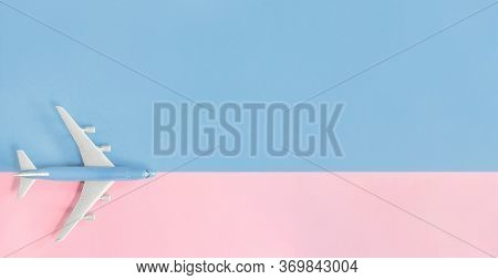 Air Flights And Travel. Blue Toy Airplane On Light Blue And Pink Matching Color Background. Flat Lay