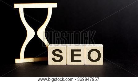 Wooden Blocks Seo With Sand Clock On Table. Personal, Career Or Business Development, Mindset Concep