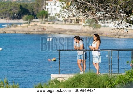 Santa Ponsa, Calvia, Mallorca, Spain - June 01, 2020: Two Women Leaning On The Railing Watching The