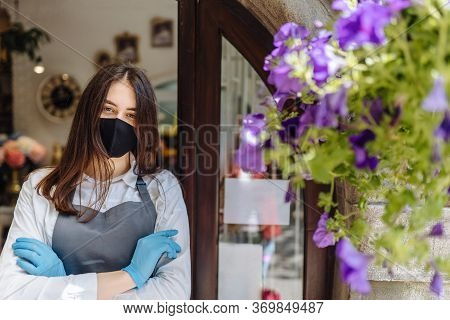 Coronavirus Covid 19. Floral Shop Woman Owner In Gloves With Face Mask, Open Door After Lockdown Qua