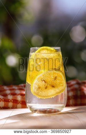Lemonade With Fresh Lemon In Glass On Garden Background.