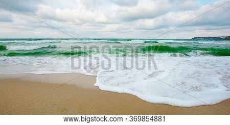 Sea Tide On A Cloudy Evening. Waves Crashing Sandy Beach