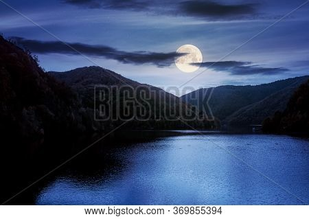 Tarnita Lake In Romania At Night. Beautiful Nature Scenery In Autumn In Full Moon Light. Gorgeous Sk