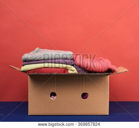 Large Brown Cardboard Box Filled With Clothes, Concept Of Moving, Volunteering And Help