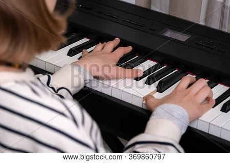 Closeup Of Teenager Playing Piano In Home Music Studio. Girl Having Online Class And Practicing On M