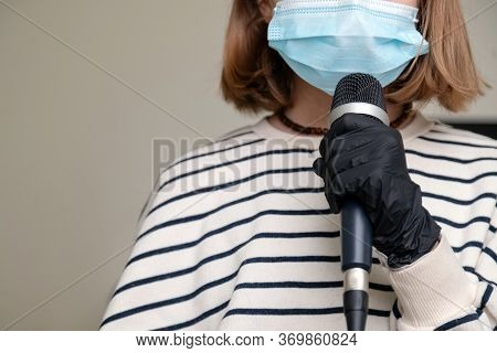 Close Up Of Musician Wearing Medical Face Mask And Holding Microphone. Concept Of Performance And Fe