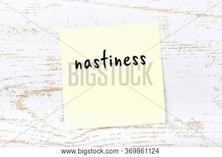 Yellow Sticky Note On Wooden Wall With Handwritten Inscription Nastiness