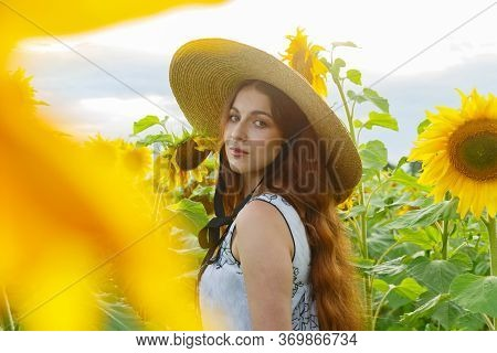 Portrait Of A Pretty Girl In A Field Of Sunflowers.
