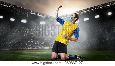 Soccer or football player wearing mask. Team sports player in medical mask emotionally kneel on stadium during coronavirus outbreak.