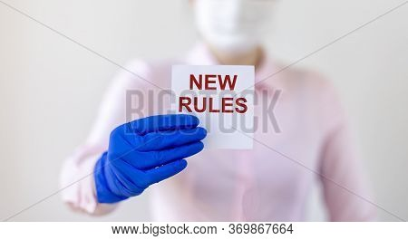 Text New Rules Written On Note Paper In Hands Of A Blurred Doctor In Gloves And Mask. New Rules Afte