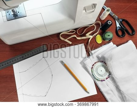 Drawing Of A Pattern Of A Medical Face Mask Lies On The Surface Of A Brown Wooden Table Near The Sew