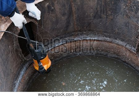 Immersion Of The Drainage Pump In A Cesspool Filled With Contaminated Water With Feces, Pumping Of H