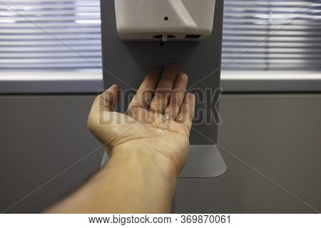 Male Hand Using Automatic Alcohol Dispenser For Cleaning Hands In The Office Or Hospital To Sanitize