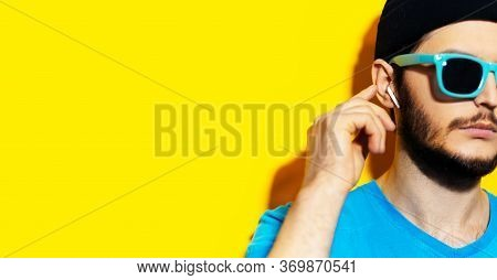 Close-up Of Young Hipster Using Wireless Earphones/earbuds, Touching It With Finger. Wearing Cyan Sh