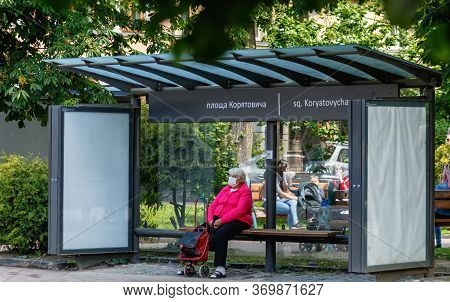 Uzhgorod, Ukraine - June 3, 2020: Elderly Woman In A Protective Mask Waiting For A Bus At The Bus St