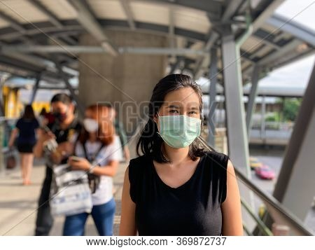 Adult Asian Thai Woman Wearing Surgical Face Mask On Public Sky Train Walkway. With Many People Blur