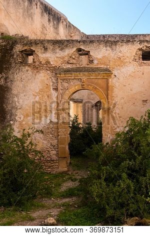 Abandoned Old Ruined Building. Gate With An Arc Without Door. Ruined Facade Of The Walls. Dar Caid H