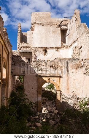 Abandoned Old Ruined Building. Gate With An Arc Without Door. Ruined Facade Of The Walls. Wild Growi