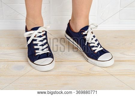 Woman Feet Shod In Classic Bllue Gumshoes With White Shoelaces And Standing On Toes On A White Wood