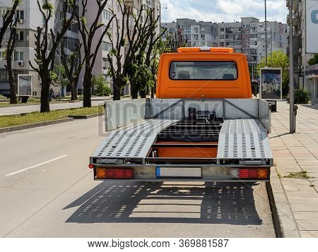 Stationary Empty Orange Car Tow Track Parked On A City Street On A Summer Sunny Day. Vehicle For Tra